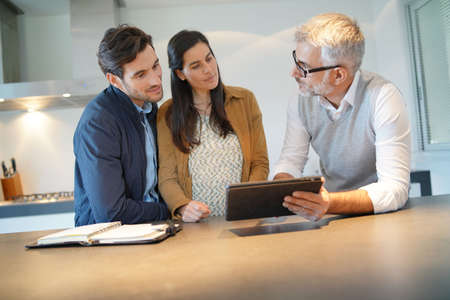 Kitchen salesman going through ideas with potential buyer couple