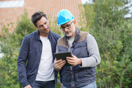 Builder going through outdoor plans with homeowner Stock Photo
