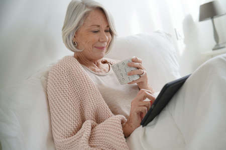 Attractive senior woman relaxing in bed with hot drink and tablet