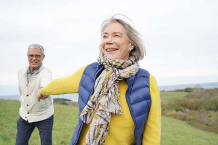 Healthy senior woman holding husband's hand and leading way on countryside walk