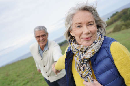 Healthy senior woman holding husbands hand and leading way on countryside walk