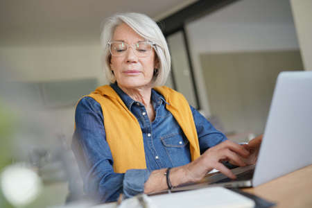 Senior woman working on laptop in modern home