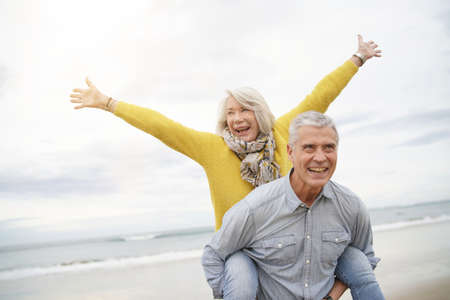 Modern vibrant senior couple piggy back riding on beach