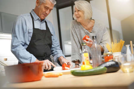 Senior couple couple cooking together in modern kitchen