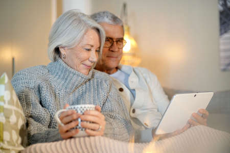 Senior couple relaxing at home on couch with tablet Imagens - 113925863