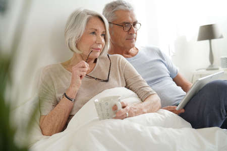 Senior couple relaxing in bed looking at tablet