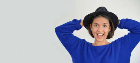 Isolated vibrant playful stunning brunette in hat looking at camera
