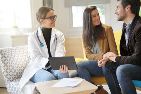 Happy doctor with couple patients in modern office