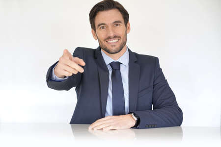 Isolated attractive businessman sitting at desk in suit pointing at camera
