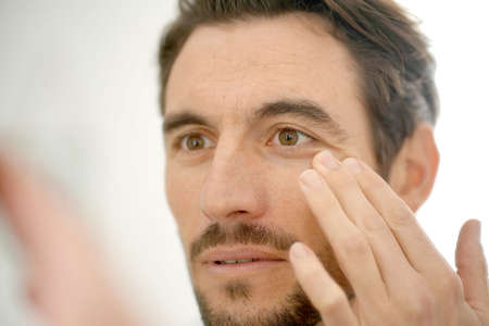 Handsome man checking wrinkles in mirror at home Stock fotó