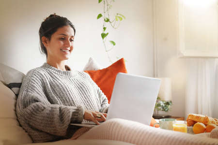 Happy attractive young woman on laptop in bed