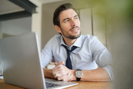 Relaxed attractive businessman working in modern office