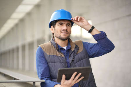 Attractive building expert in hardhat checking sight with tablet