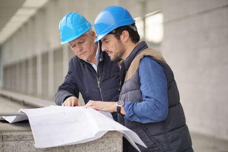Workmen in hard hats consulting over blueprint on modern building sight Reklamní fotografie