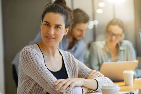 Focus on attractive brunette looking at camera in co working space Reklamní fotografie