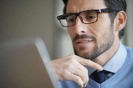 Portrait of attractive man working on laptop wearing glasses