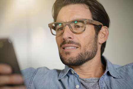 Portrait of casual handsome man checking cellphone and wearing designer glasses