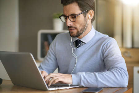 Businessman working on laptop with headphones in office