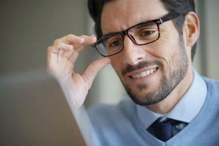 Portrait of attractive man smiling working on laptop wearing glasses