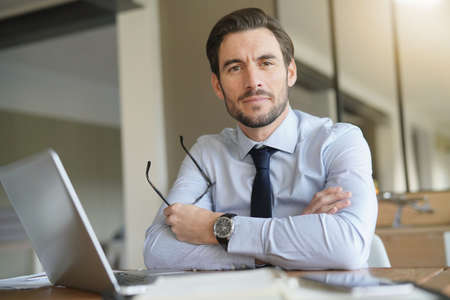 Smart handsome businessman in office with laptop looking at camera