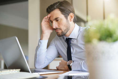 Stressed handsome business man looking at laptop in office