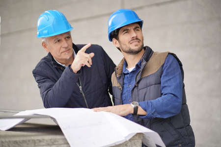 Workman pointing and showing something to employee on modern building sight Reklamní fotografie
