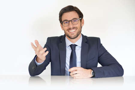 Isolated attractive businessman sitting at desk in suit
