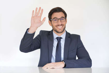 Isolated attractive businessman sitting at desk in suit waving at camera Reklamní fotografie