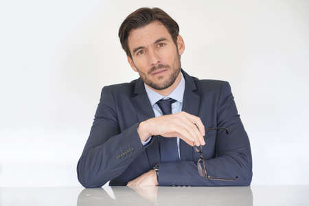 Isolated attractive serious businessman siting at desk in suit
