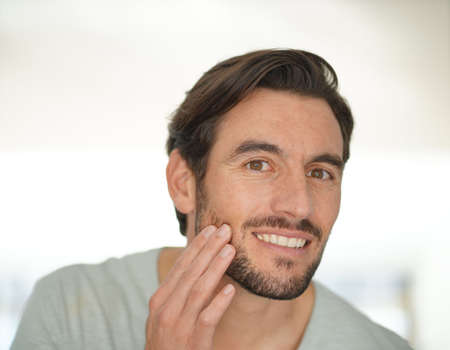 Portrait of attractive man checking wrinkles looking at camera Reklamní fotografie