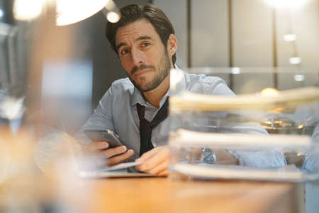 Handsome businessman working late checking cellphone in modern office