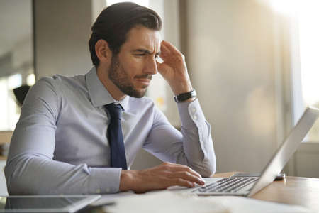 Handsome businessman concentrating on laptop in modern office