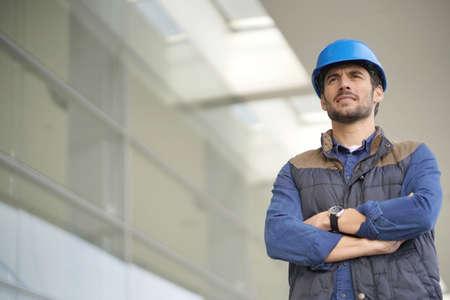 Industrial worker in hardhat infront of modern building