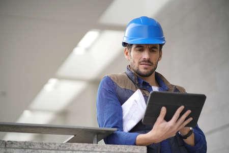 Handsome building expert in hardhat outdoors with tablet and blueprint Reklamní fotografie