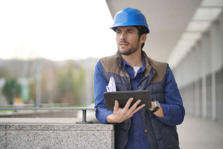 Handsome building expert in hardhat outdoors with tablet and blueprint 写真素材 - 113990057