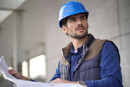 Attractive architect in hardhat checking blueprints outdoors
