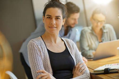 Focus on attractive brunette looking at camera in co working space Stock Photo