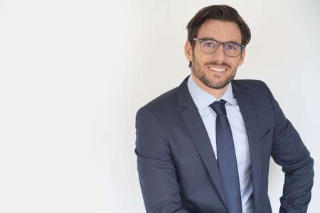 Isolated attractive businessman sitting in suit wearing glasses Reklamní fotografie