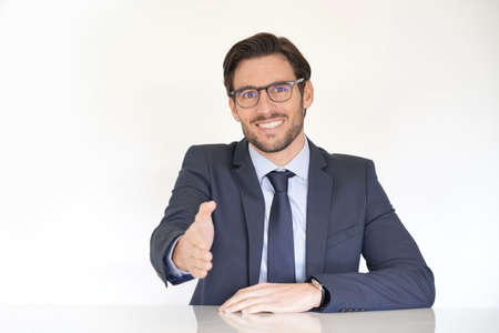 Isolated attractive businessman sitting at desk in suit with extended arm Reklamní fotografie