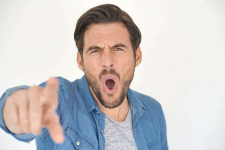 Portrait of handsome man shouting and pointing on white background Reklamní fotografie