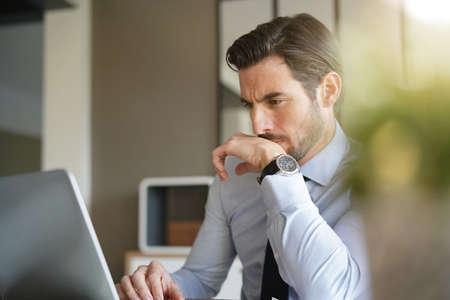Handsome businessman working on laptop in modern office