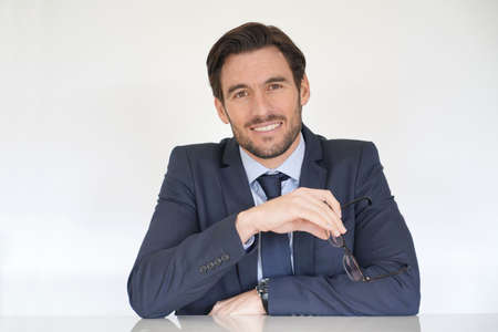 Isolated attractive businessman siting at desk in suit