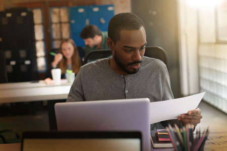 Young attractive black man looking over documents in modern office