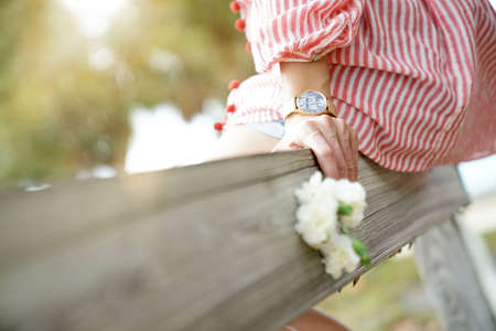Close up of woman sitting on rustic fence holding flowers 写真素材