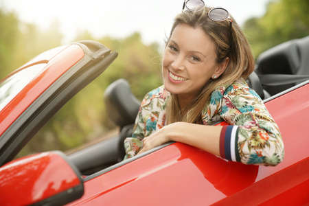 Portrait of smiling young woman in red convertible car