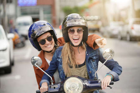 Happy young women riding scooter together in city Foto de archivo