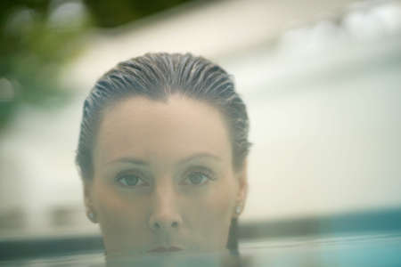 Portrait of elegant young woman in swimming pool with red lipstick