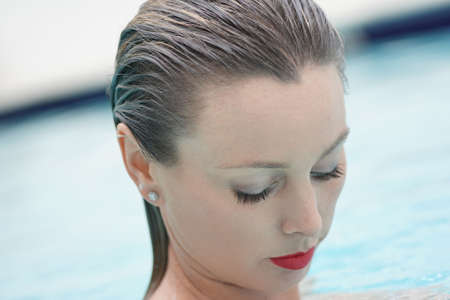 Portrait of stunning woman in swimming pool with red lipstick