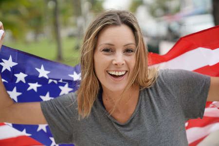 Gorgeous dynamic young woman smiling with big American flag outdoors