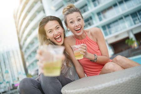 Dos amigos divertidos atractivos de fiesta con bebidas en el bar de la azotea en la ciudad
